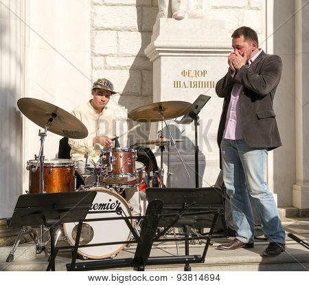 Street Musicians Performing On Drums And Harmonica