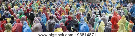 Crowd in colorful plastic raincoat ponchos