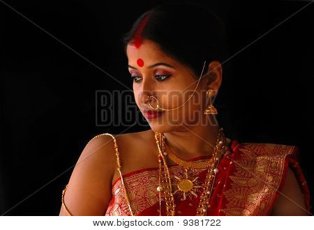 Woman with red sari and gold jewellery