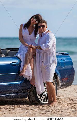 Beach Couple Near Convertible Car On The Beach