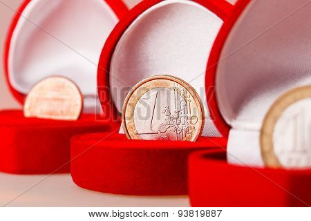 Red Gift Boxes With One Euro, Ten Roubles And One Cent Coins. Focus On Euro Coin