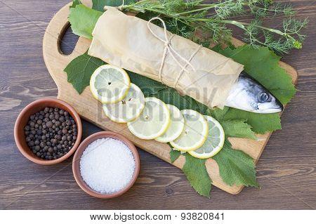 Fresh mackerel on paper in grape leaves