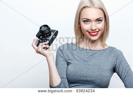 Smiling blond-haired woman posing with camera