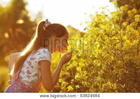 Little Girl Sniffing A Yellow Flower