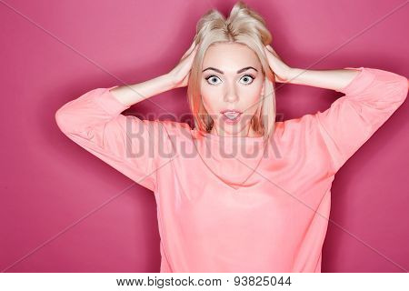 Amazed young woman touching her hair