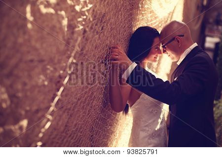 Bride And Groom Against A Wall With Trammel