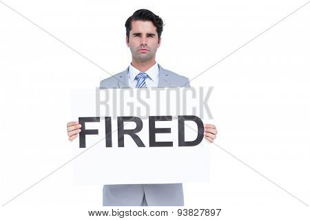 Sad businessman holding a fired sign on white background