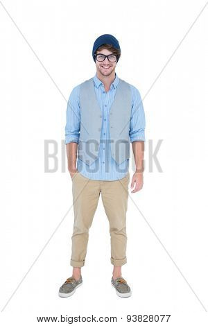 Geeky hipster looking at camera with hand in pocket on white background