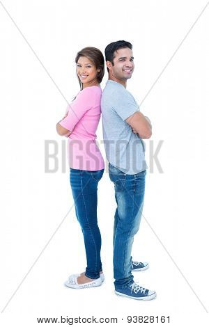 Happy couple standing back to back on white background