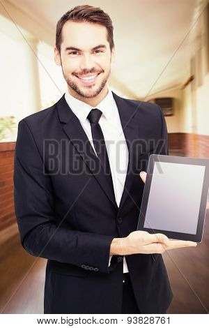Smiling businessman showing his tablet pc against hallway