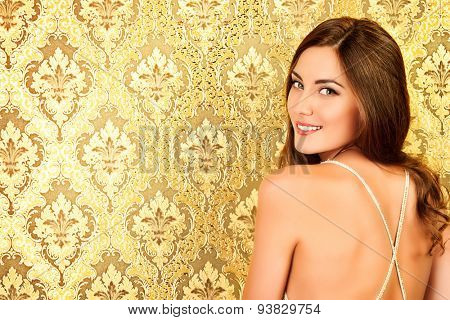 Elegant young woman in  evening dress posing in vintage interior. Fashion shot.