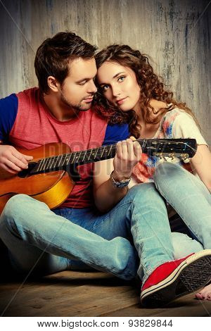 Romantic young man playing the guitar to his beloved girl. Happiness. Love concept.