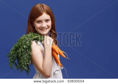 Smiling girl holding bunch of carrot