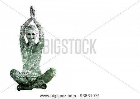 Sporty woman sitting in Namaskar pose with twisted hands against beautiful pink leaved trees
