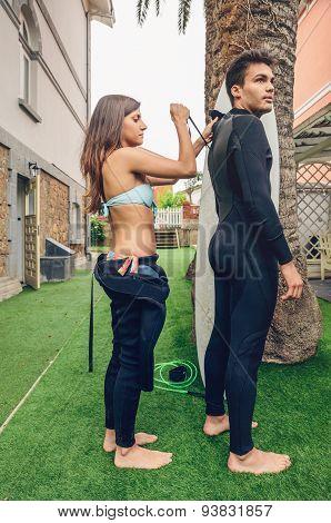 Surfer woman with bikini closing man wetsuit