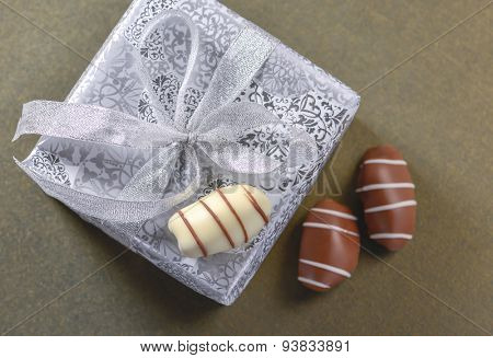 A solver gift box and three date fruit chocolates from top angle.