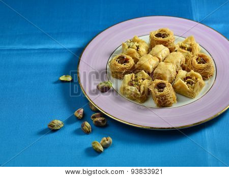 Baklawa in a plate with few whole pistachio nuts scattered on blue background.