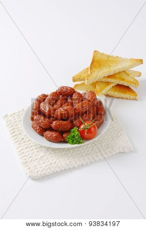 plate of mini sausages and crispy toasts on white table mat