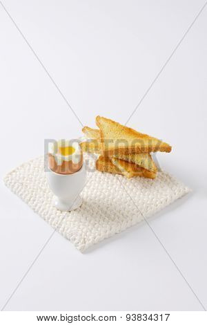 soft boiled egg in egg cup and crispy toasts on white table mat