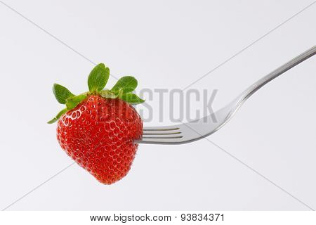 close up of red strawberry on silver fork