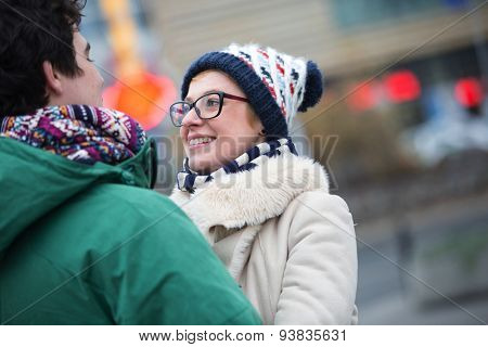 Romantic couple looking at each other in city during winter