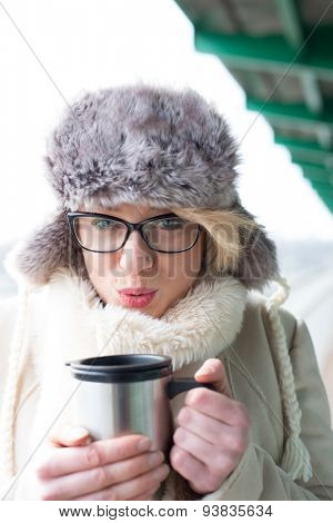 Portrait of woman blowing coffee in insulated drink container during winter
