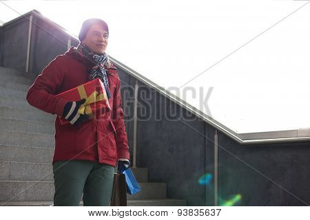 Smiling man holding gifts while moving down steps