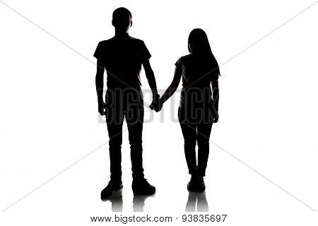 Silhouette of teenagers holding hands
