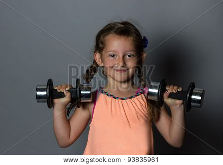Young Smiling Girl Lifting Dumb Bell