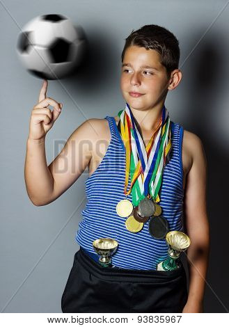 Young Winning Boy With Cup And Medals Spinning The Ball