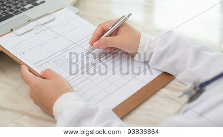 Hand of doctor writing on prescription