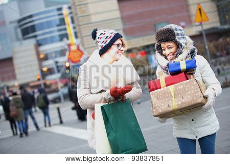 Happy women with gifts and shopping bags walking on city street during winter
