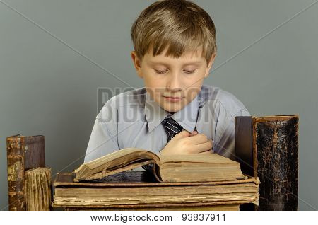 The boy attentively reads the old book