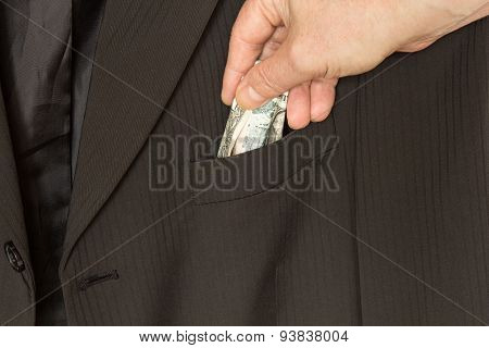 Bribery, hand puts money in a suit pocket