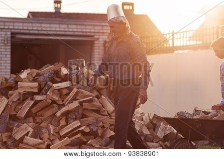 Smiling Senior In Front Of Stack Of Wood