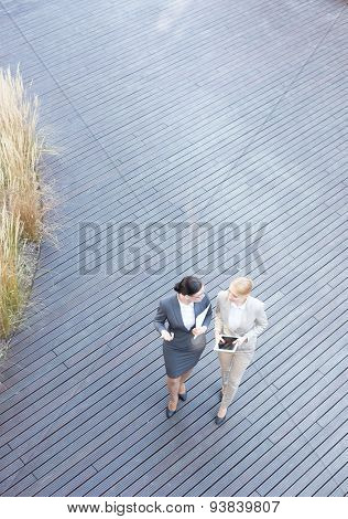 High angle view of businesswomen discussing while walking on floorboard