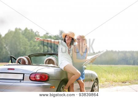 Woman showing something to friend with map while leaning on convertible