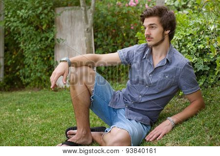 young casual man posing seated, smiling at the camera, outdoors