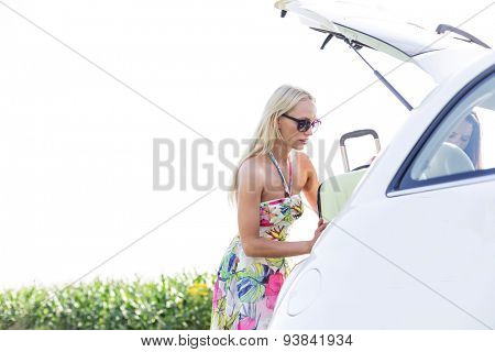 Female friends loading luggage in car trunk against clear sky