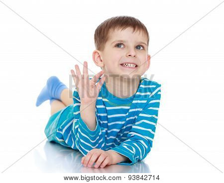 The little boy waved his hand lying on the floor