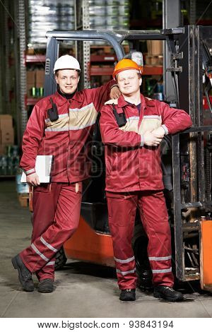 happy smiling warehouse workers in uniform in front of forklift stacker loader