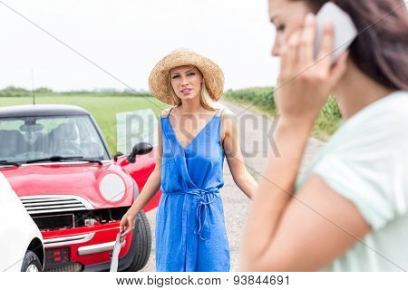 Angry woman looking at female using cell phone by damaged cars on road