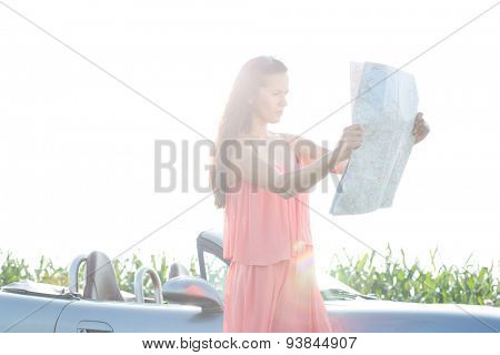 Woman reading map while standing by convertible against clear sky