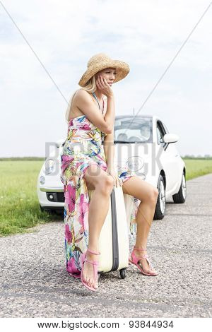 Full length of irritated woman sitting on luggage by broken down car