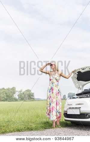 Woman shielding eyes while standing by broken down car on country road