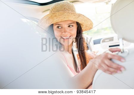 Happy woman looking back while driving car