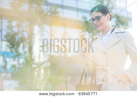 Businesswoman using smart phone on sunny day