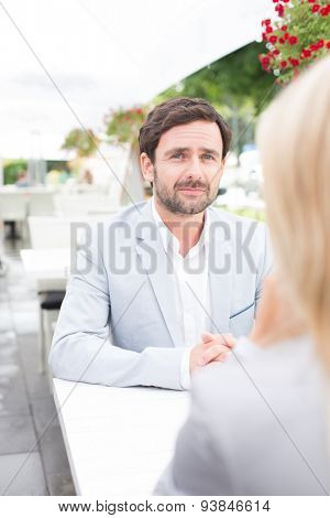 Thoughtful businessman sitting with female colleague at sidewalk cafe