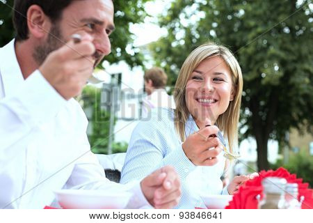 Happy businesswoman eating food with colleague at sidewalk cafe