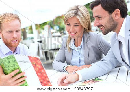 Businesspeople deciding menu at sidewalk cafe